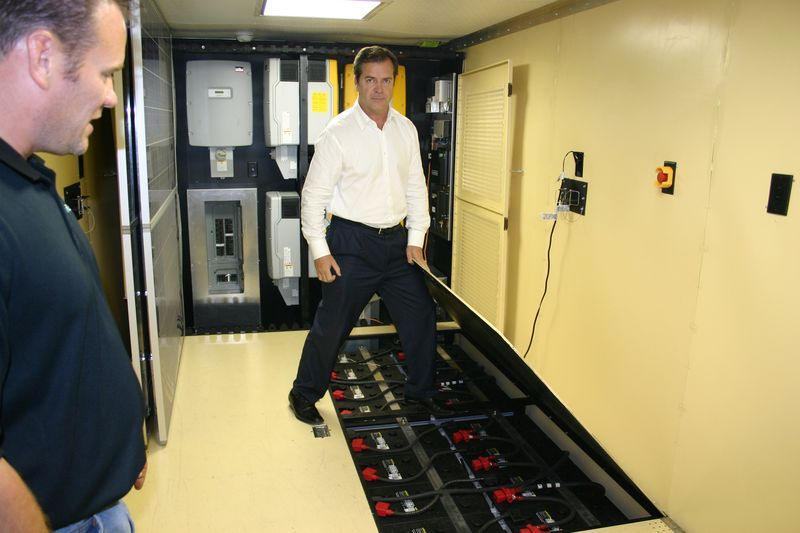 SunDial President Dan Rice (center) displaying a mobile solar unit's rechargeable battery reserves