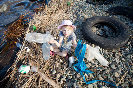 Young blonde girl collecting trash alongside a river