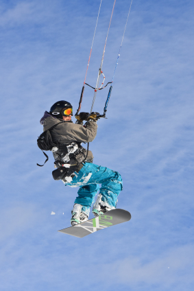 Snowkiter jumping with a snowboard